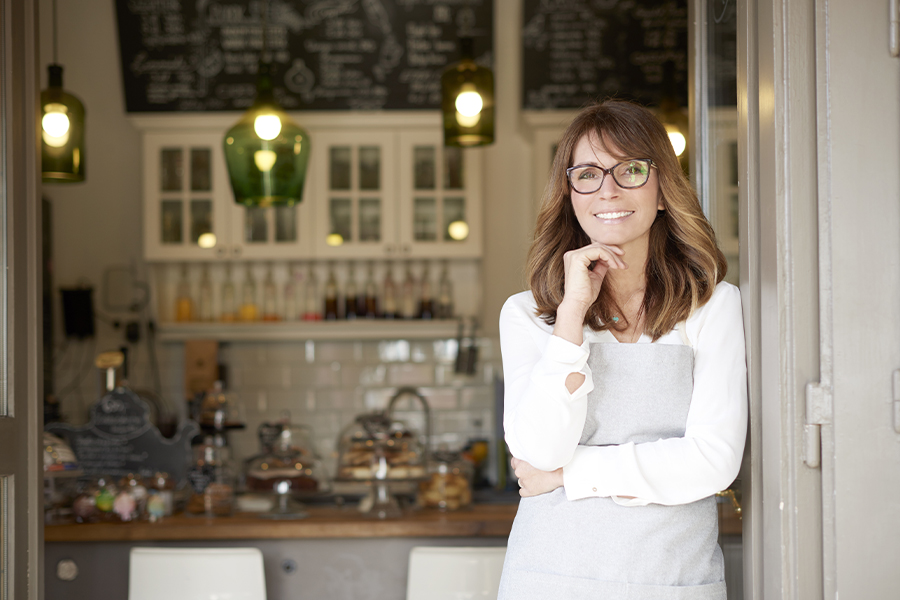 Business Insurance - Cafe Owner Standing in the Doorway of Her Coffee Shop