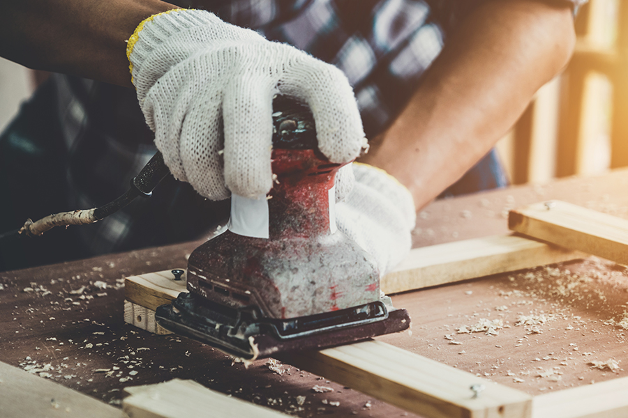 Specialized Business Insurance - Closeup of Carpenter Working at Workshop Using Professional Tools