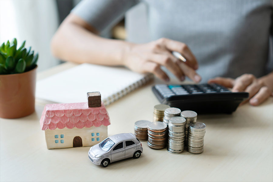 Bundling Home and Auto Insurance - Picture of a Womans Hands with a House and Car on the Desk